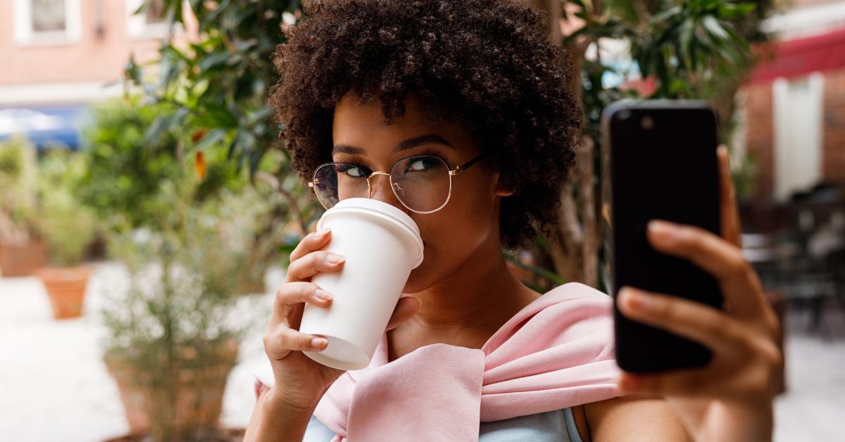O femeie care bea cafea în timp ce se pozează
