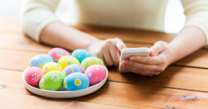 Decorated Easter eggs near a person holding a phone