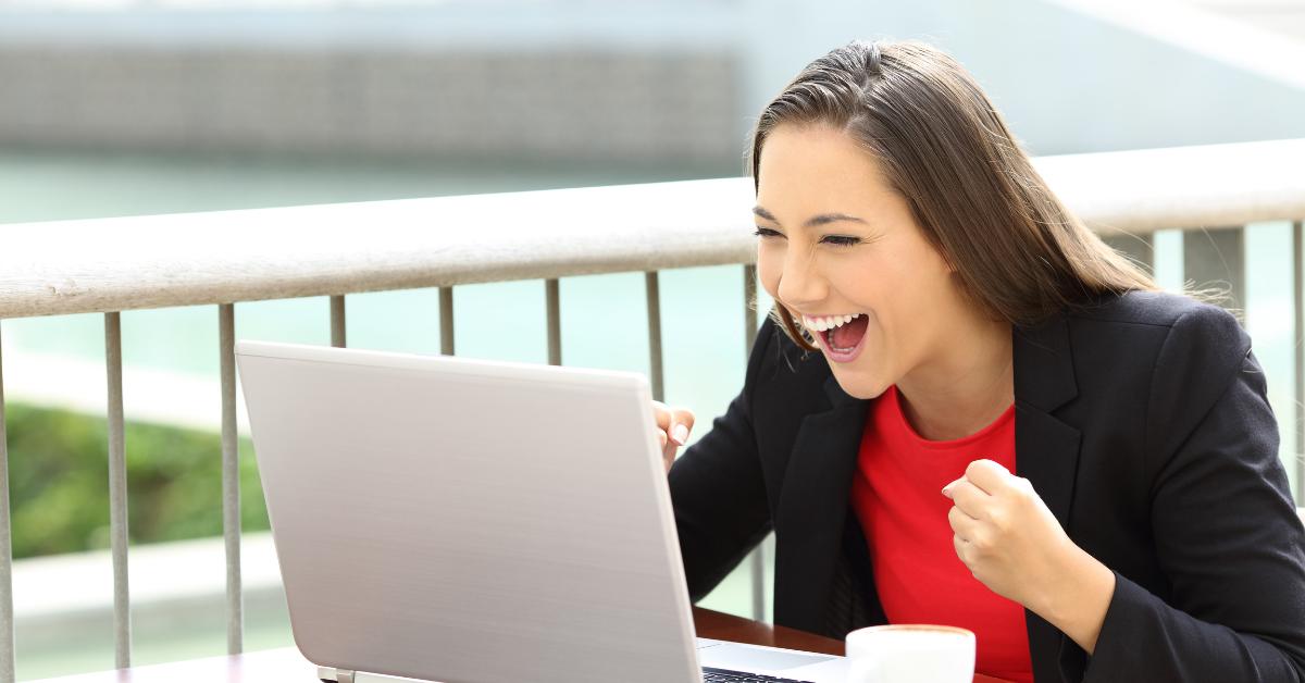 Femeie exaltată uitându-se la un monitor