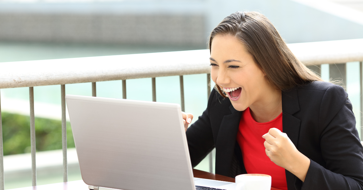 excited woman looking at a laptop