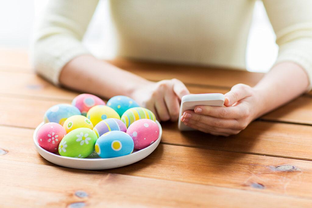 Ouă decorate de Paște alături de o persoană cu un smartphone