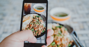 A person taking a picture of a dish