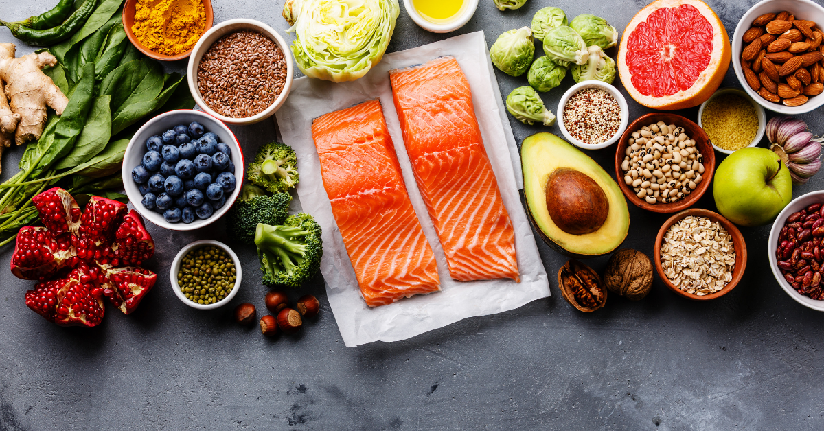 a table full of healthy food such as salmon and avocado