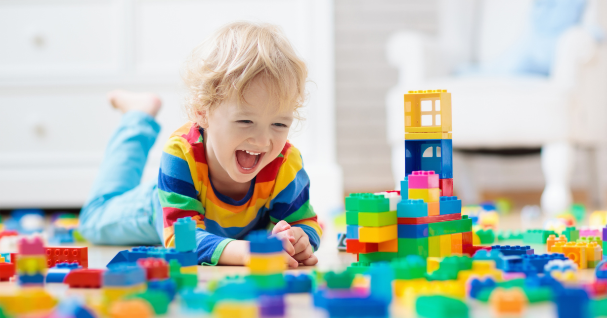 Extatic kid playing with lego