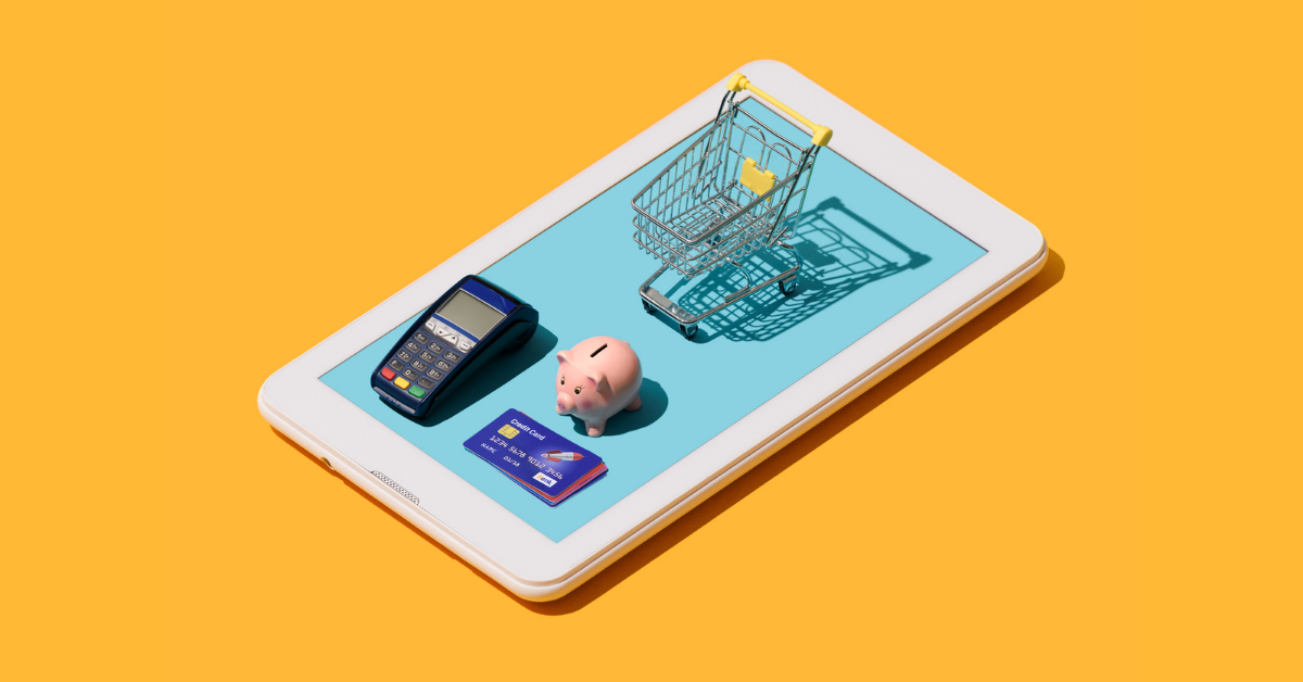 A shopping cart, a piggy bank and a credit card placed on a tablet