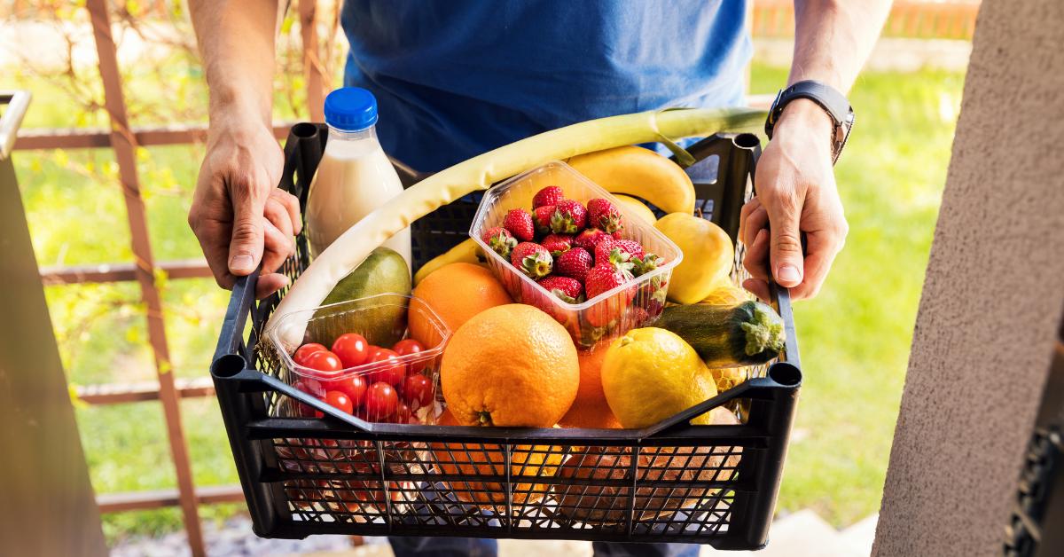 man holding a basket of produce