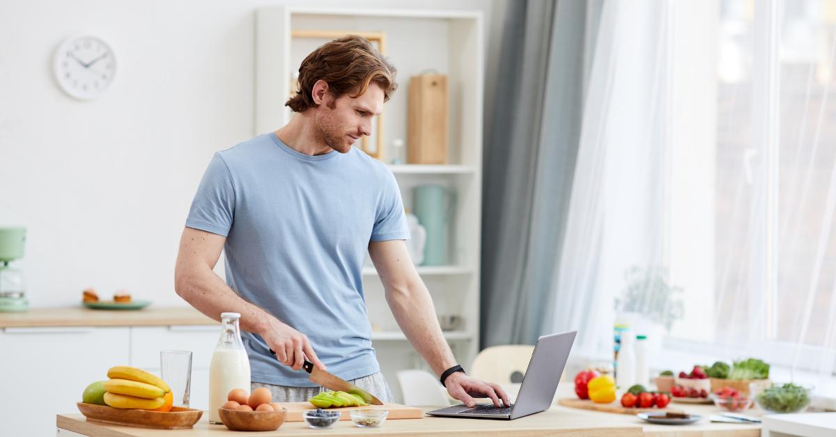 Un bărbat gătind în timp ce folosește un laptop