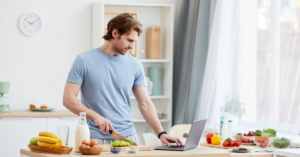 A man cooking while using a laptop